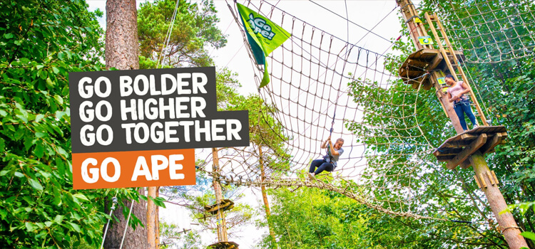 Two young women navigate a zipline obstacle course