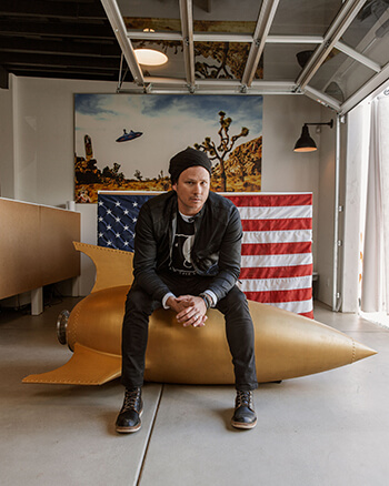 To the Stars founder Tom DeLonge sits atop a model rocket, behind him is an American flag draped over a dresser and a painting of a UFO in the desert.