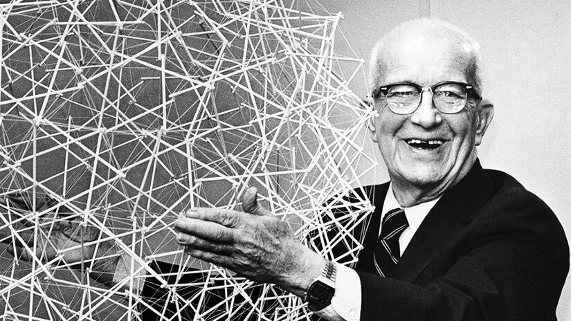 Buckminster Fuller smiling and holding a wirefram version of his famous Buckyball
