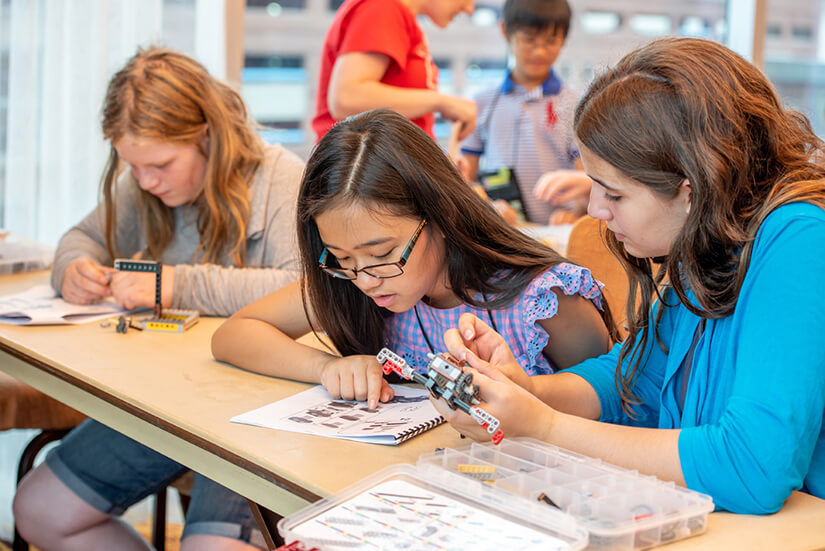 Several young girls work together to build a LEGO car