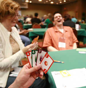 People playing a card game, a hand in the foreground holding cards while a man in the background laughs