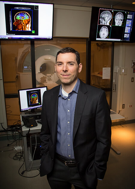 Portrait: Dr. Barbey stands in the lab, standing in front of an fMRI machine.